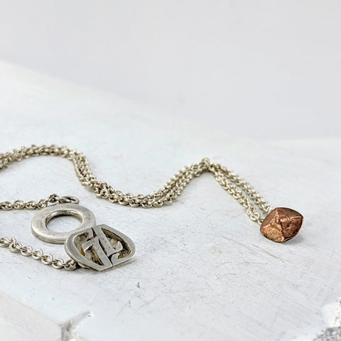 This necklace has a small copper pendant which is square with four rough facets . The chain is sturdy and there is a feature catch with a large loop and toggle in the shape of two G's.