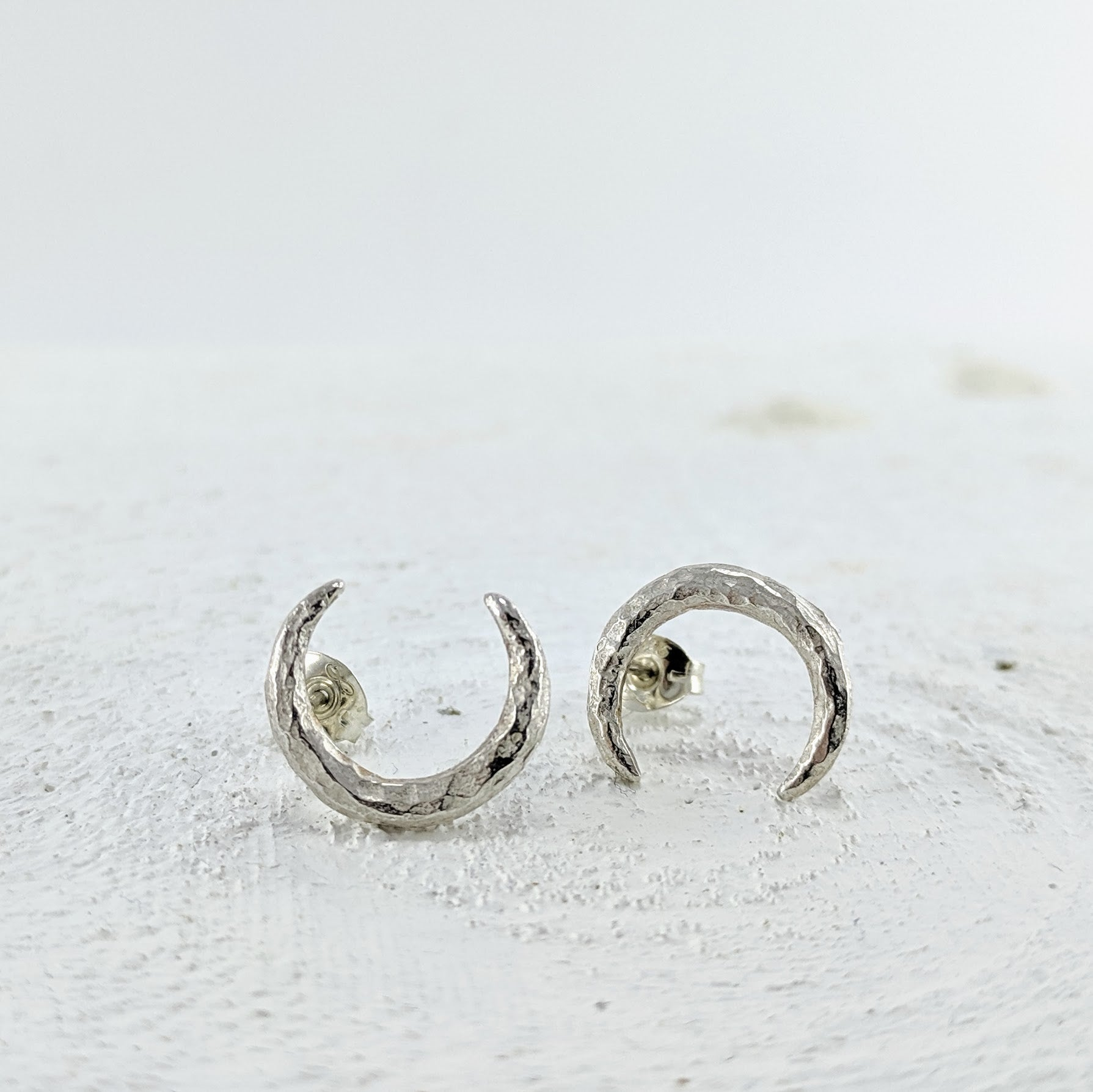 These silver stud earrings are handmade by Tom Richards. They are small hammer textured crecents with silver posts and butterfly backs.
