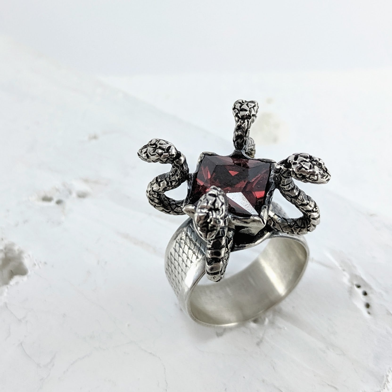 A silver ring by NZ jeweller Nick Rule. The band has a fine texture around the middle. Four carved snakes hold up a square dark red gemstone. It has an aged patina.