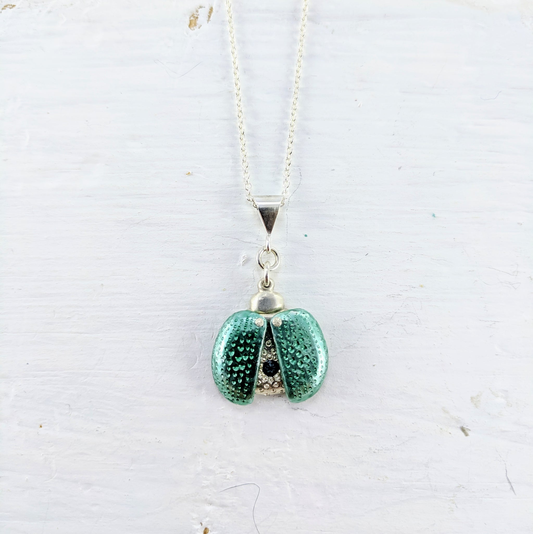 This is a solid silver pendant in the shape of a small  ladybug hanging on a fine chain. It has pale green coloured wings which open up to show a small round  green gemstone.  By Adele Stewart.