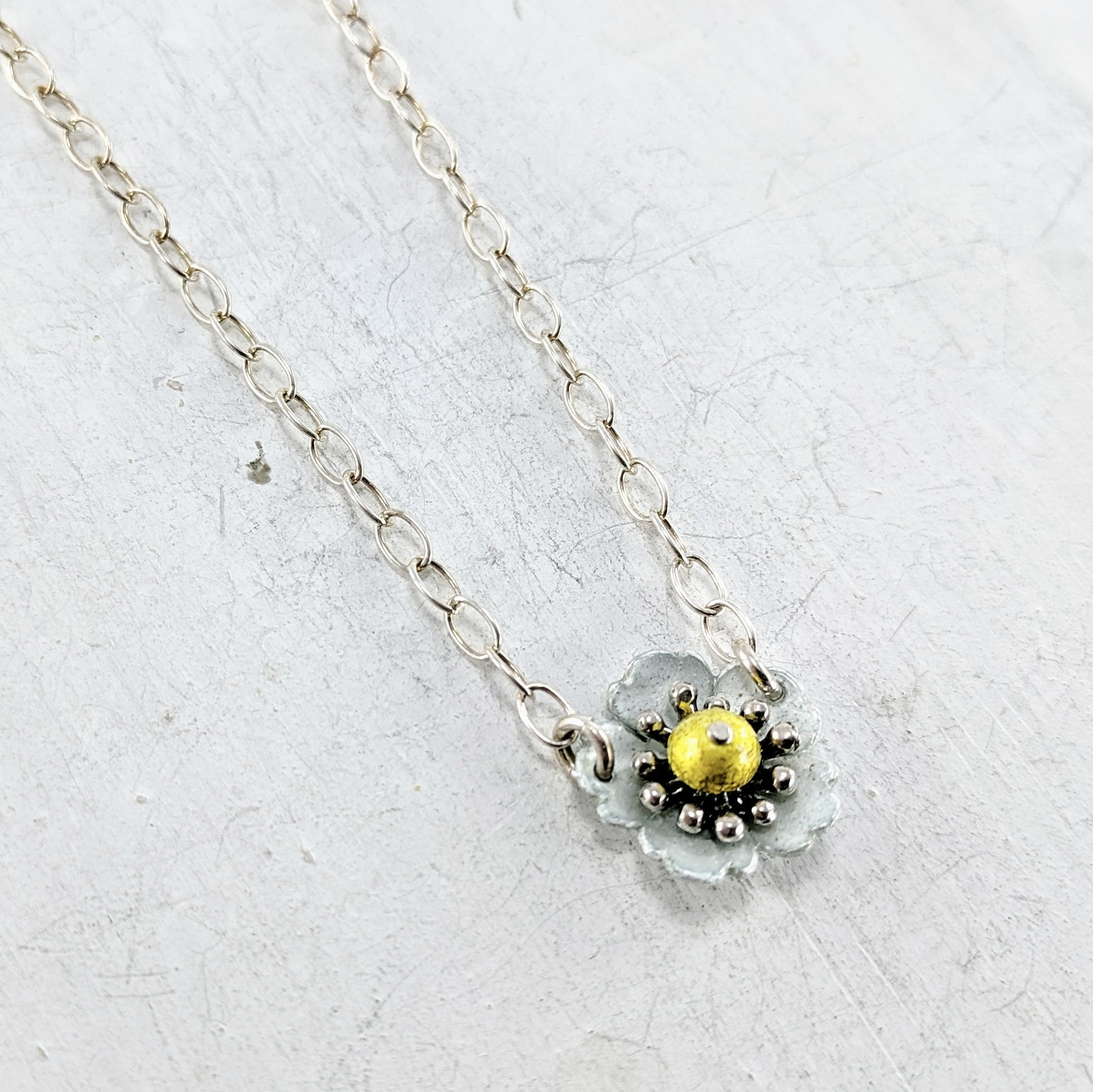 Handmade in New Zealand, this is a silver necklace with a enamelled fine silver alpine strawberry pendant yellow and blue