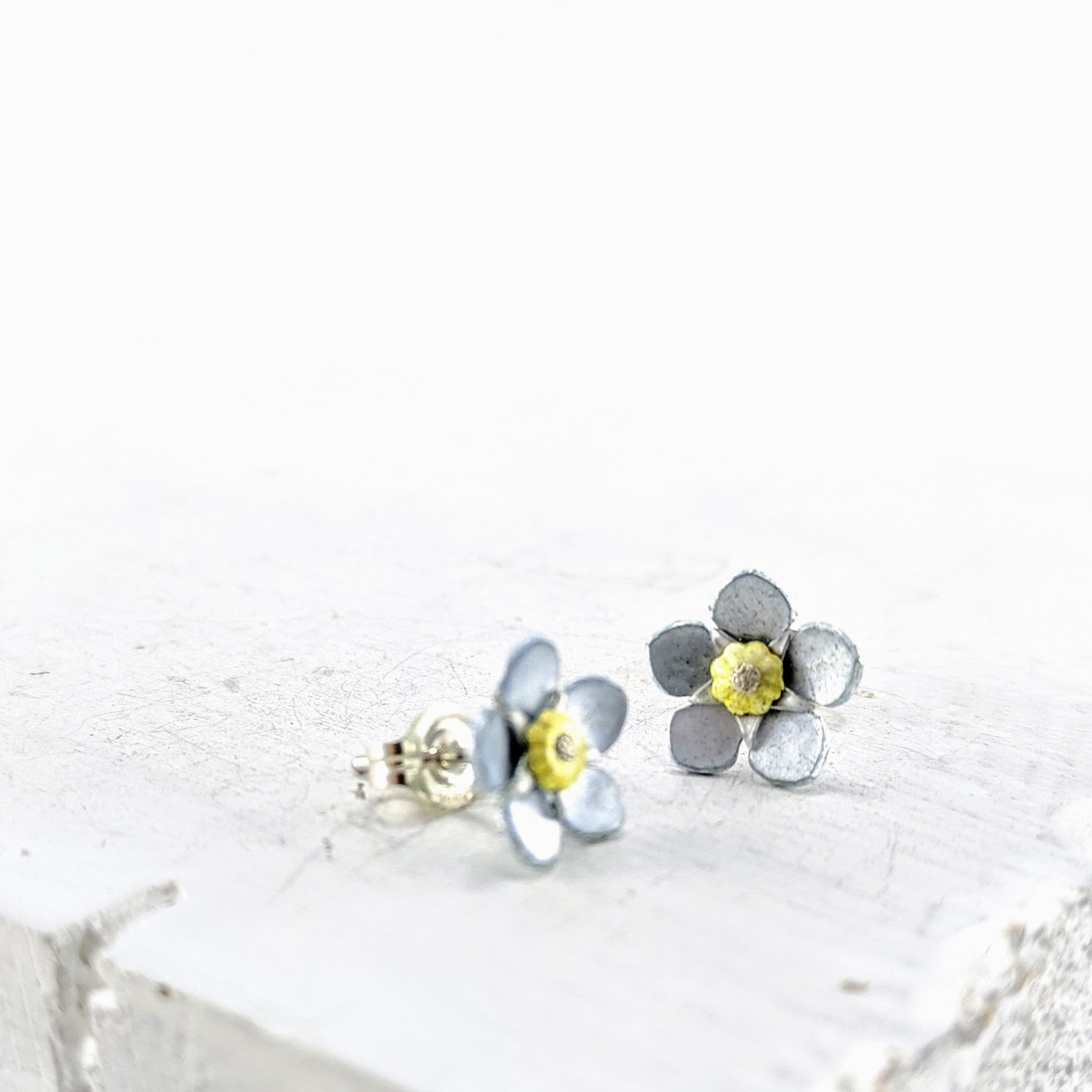 Unique jewellery handmade in New Zealand by Adele Stewart Maker.  These studs are pale blue and yellow enamel on fine silver.  They are forget-me-not flower studs.