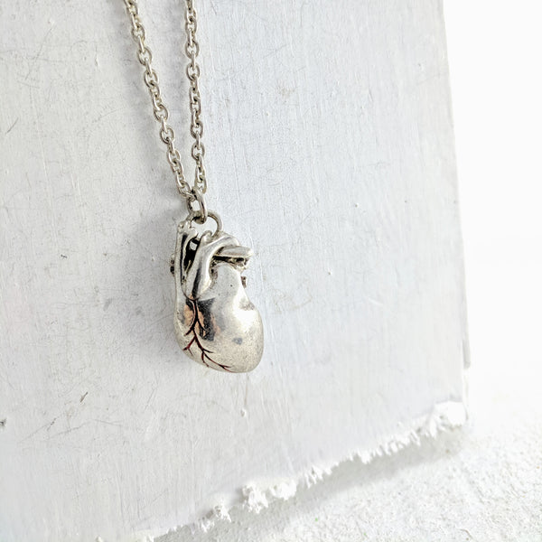 Handmade in New Zealand, this is a silver necklace with an anatomical heart pendant and red enamel detailing.