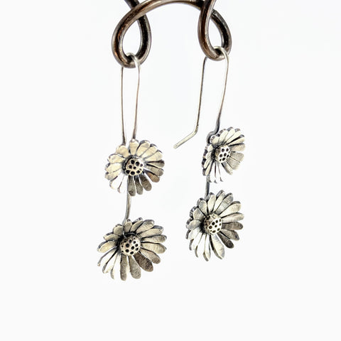 These drop earrings are shaped as two medium sized daisies with linked stems. They are sterling silver with an antiqued finish. By Rebecca Fargher.