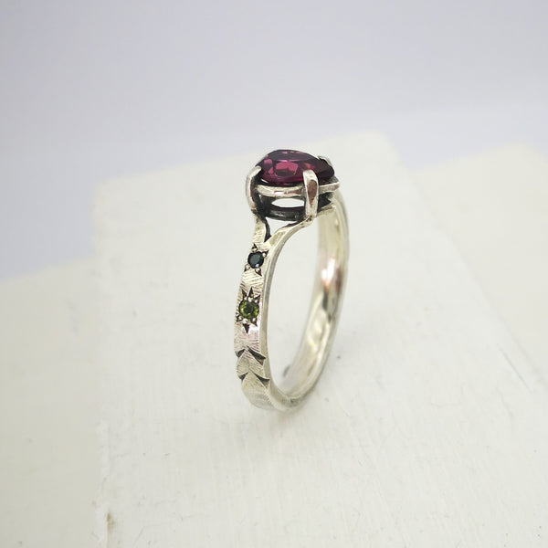 Pear shaped pink garnet ring with green sapphires and black spinel on the shoulders. Silver ring by Vaune Mason.