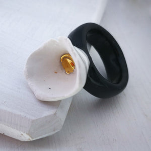 A handmade porcelain ring by NZ jeweller Marita Green. A cream lily with a golden dot in the centre on top of a black band.