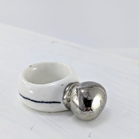 A white porcelain ring with a  thick platinum coloured  bauble on top, and a black line around the outside of the band. By NZ jeweller Marita Green.