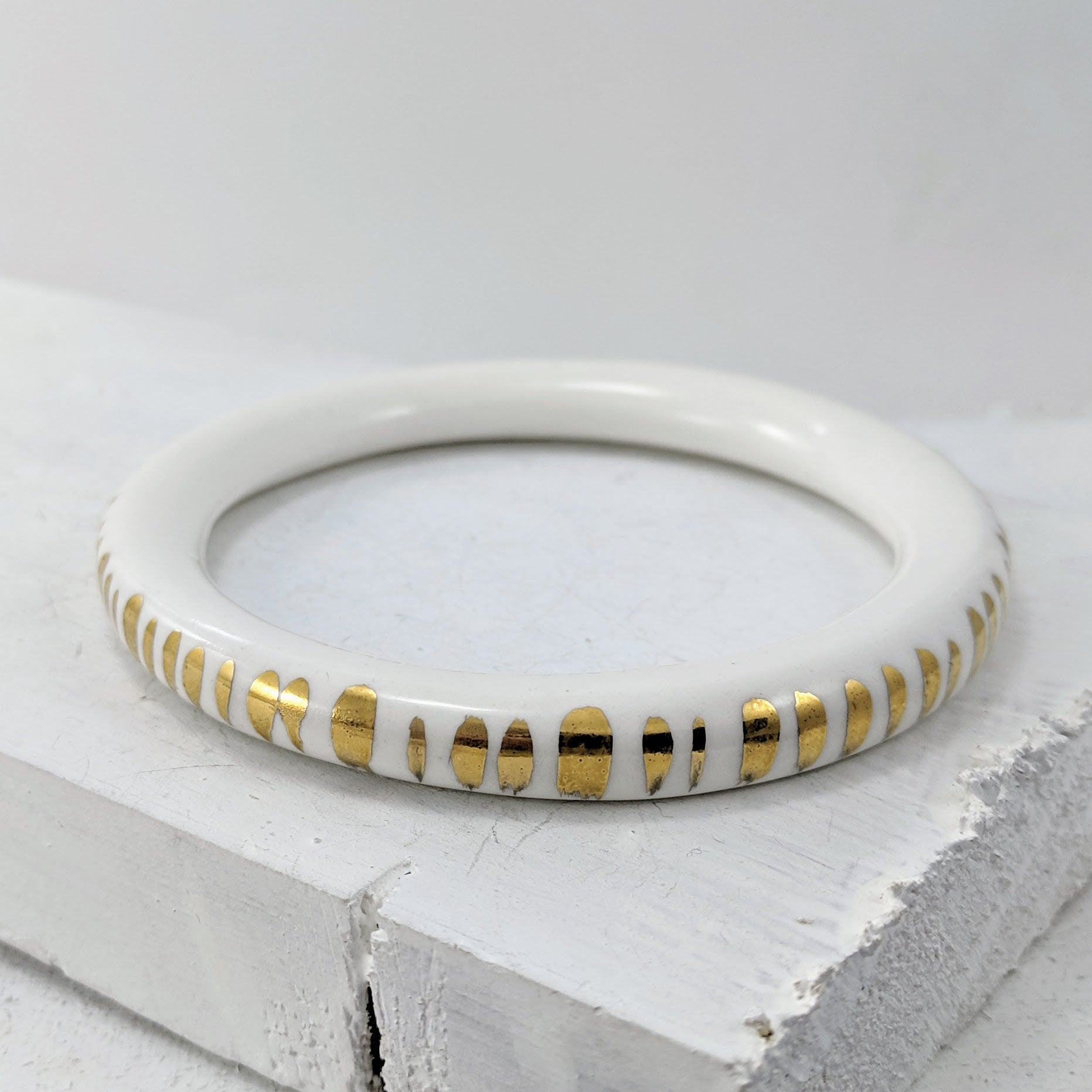 Unique jewellery handmade in New Zealand by Marita Green. White porcelain bangle with a smooth shiny finish and thick gold foil dashes on the outer surface