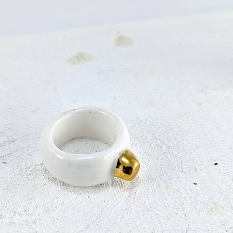 This porcelain ring is hand made in NZ. The band is a chunky cream and a small gold bump sits on top. By Marita Green.