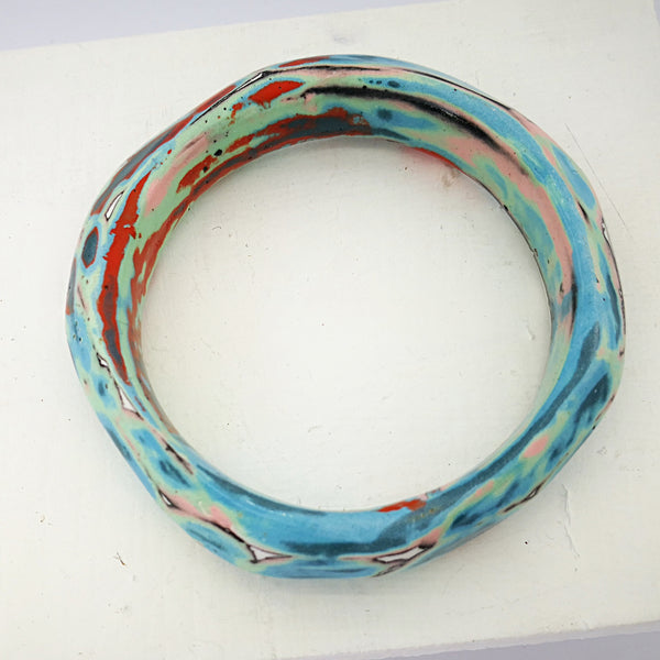 A roughly round porcelain bangle with splashes of pale green, blues, reds, pinks, white and dark grey. By Marita Green.