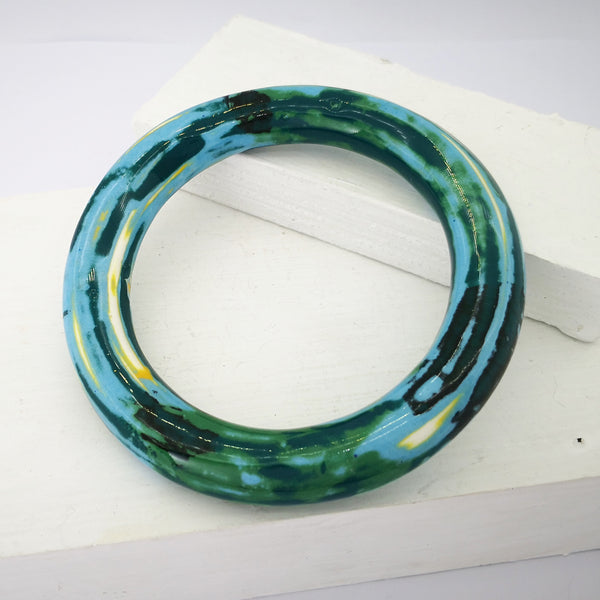 This round chunky bangle is mottled with dark green, pale blue, light yellow and white glazes over the whole surface. By Marita Green.