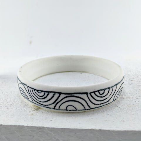 Unique jewellery handmade in New Zealand by Marita Green. White/cream porcelain bangle with a smooth matte finish and matte black wave designs on the outer surface