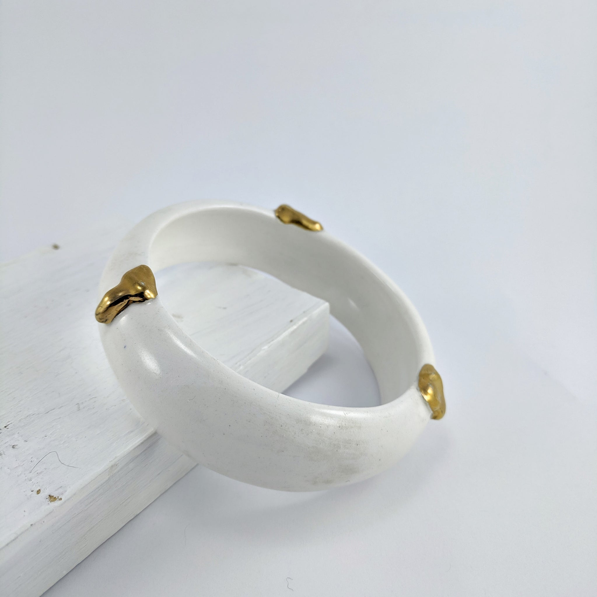 Unique jewellery handmade in New Zealand by Marita Green. White porcelain bangle with a smooth shiny finish and thick gold foil dripping down the bangle's side on the outer surface