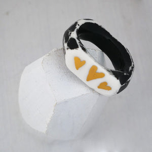 A handmade porcelain ring by NZ jeweller Marita Green. Black painted white porcelain with three gold hearts on top.
