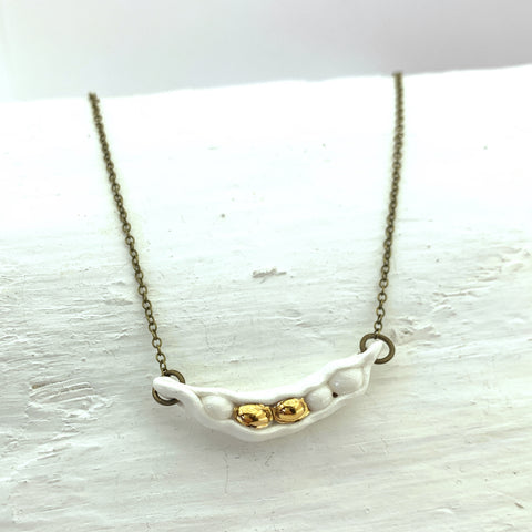 A handmade porcelain necklace by NZ jeweller Marita Green. A white and gold porcelain pea-pod on a brass chain.