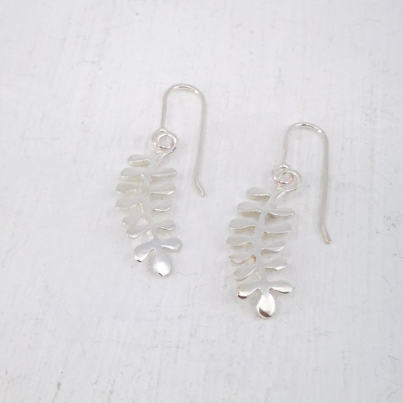 The Kowhai Leaf Earrings in sterling silver, hand crafted in NZ by Ruru Jewellery.