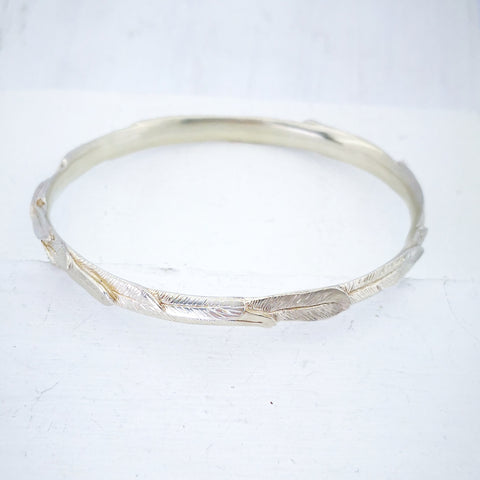 This is a slender solid silver bangle carved all the way around with feathers. The bangle is oval in shape, and is in a bright silver finish. Handmade in NZ by The Wild Jewellery.