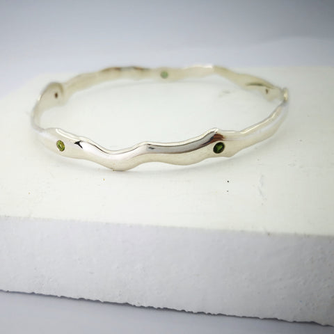 Silver molten bangle set with faceted stones. Handmade by Zoë Porter.