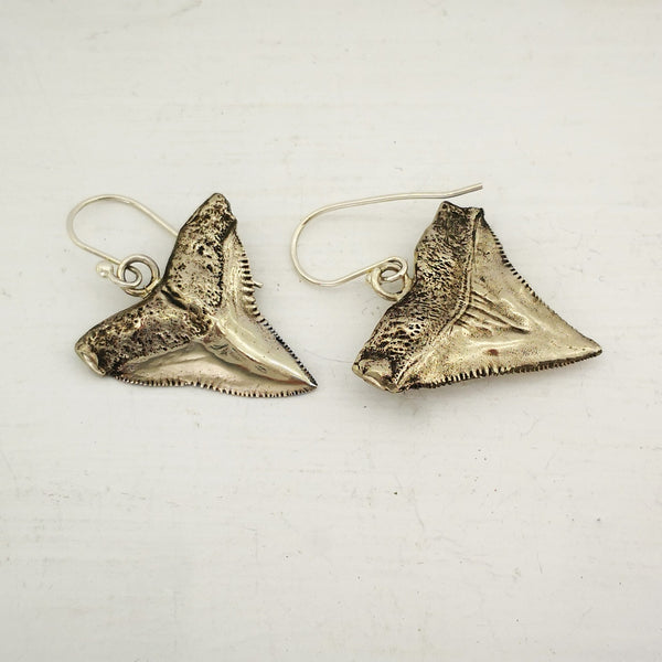 The front and back of the white bronze shark teeth earrings. By Keri-Mei Zagrobelna