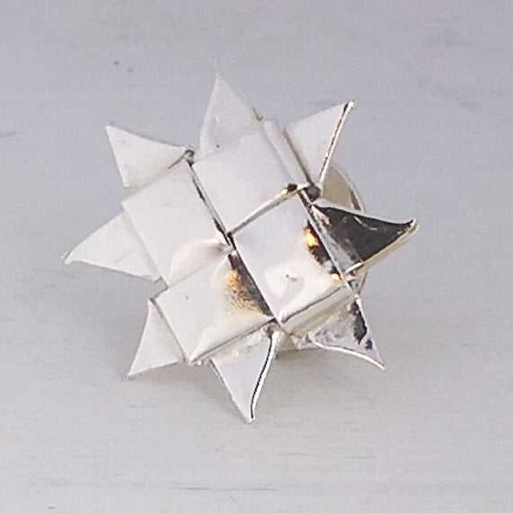 A hand-woven metal star pin by Keri-Mei Zagrobelna, made from fine silver and sterling silver strips.