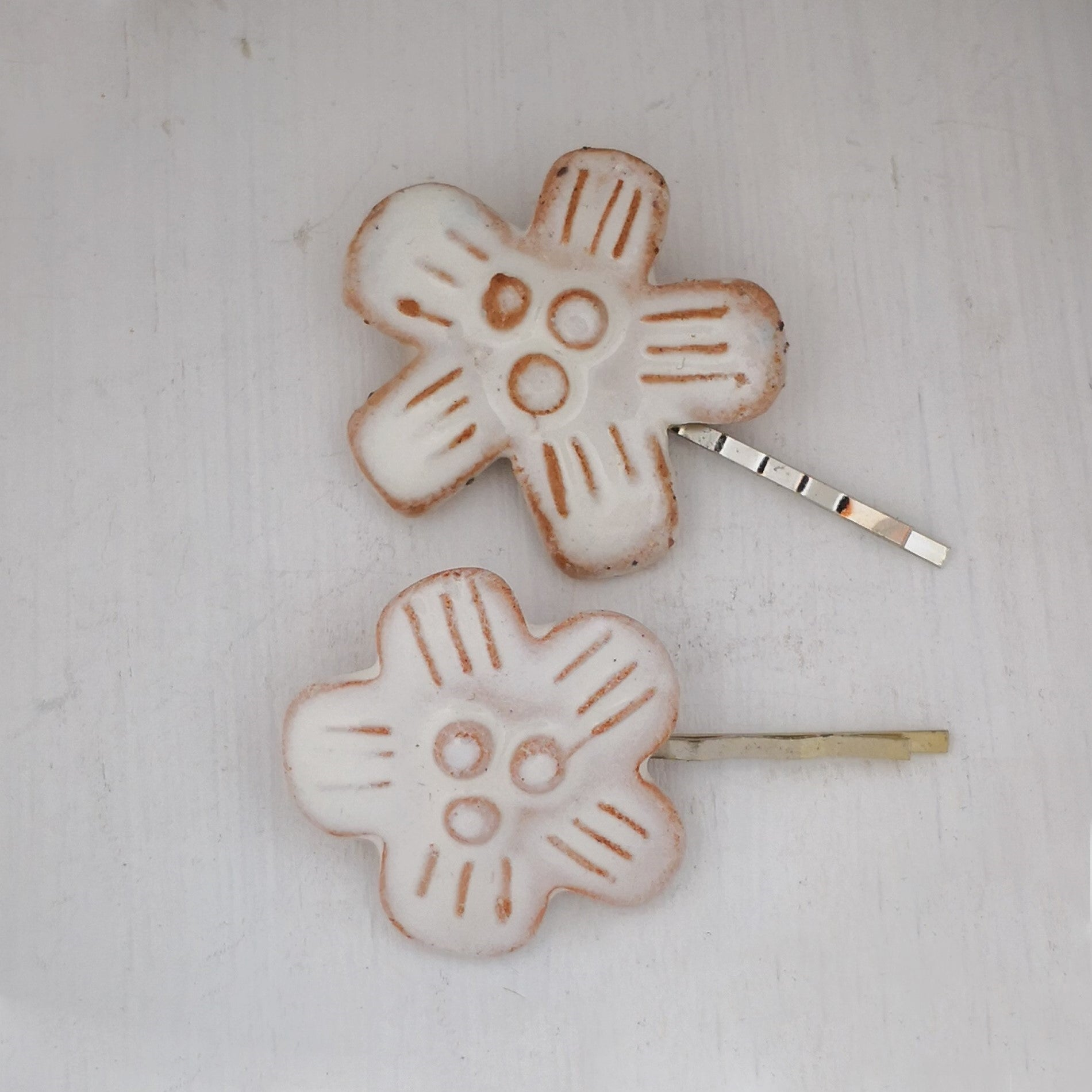 Two handmade ceramic hair clips by NZ jeweller Marita Green. White glazed ceramic flowers on metal hair slides.