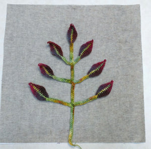 Image of floral stem and leaf crochet motif applique arranged symmetrically on stabilized pillow cover panel
