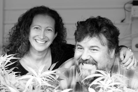 black and white photo of woman with curly hair and male with dark hair founders of company smiling with hemp plants