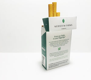 Product displayed resembles a white classic cigarette pack with a large seed/stem logo that is various shades of textured green.  The company logo is on the front flap and the text is in green label with font Manrope.  The pack is shown at an angle with the back panel facing out.  The text describes the story of the smokes.  There is a small hemp leaf dividing the paragraphs