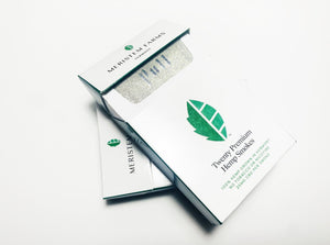 Product displayed resembles a white classic cigarette pack with a large seed/stem logo that is various shades of textured green.  The company logo is on the front flap and the text is in green label with font Manrope.  Pack is shown in plan view, front flap is partially open to reveal the silver foil that is labeled 'Pull' There are two packs shown on angled on top of the other.