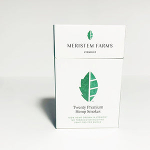 Product displayed resembles a white classic cigarette pack with a large seed/stem logo that is various shades of textured green.  The company logo is on the front flap and the text is in green label with font Manrope.  Pack is viewed from the front on a white background.