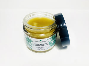 open glass jar reaveals golden coconut oil infused with hemp with white label includes green botanical drawings of hemp or cannabis plants with label text in black along with company logo.  Jar lid is black.  Photo is on a white background.
