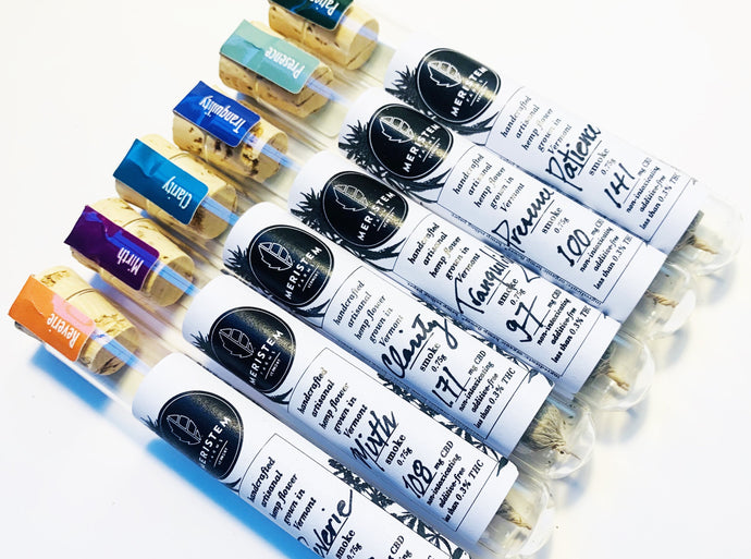 Six glass vials with white label and black print. Black Meristem Farms logo with handwritten name of each product, Reverie, Mirth, Clarity, Tranquility, Presence, Patience. Tamper strips are used to close cork tops each of distinct colors to identify each Intention which also represents a plant variety. Colors are, in the same order of the intentions listed previously; orange, purple, turquoise, deep blue, sea foam green, dark green.