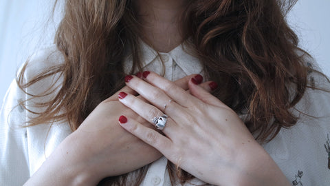 woman wearing silver-colored ring holding her chest