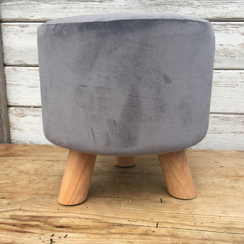 Soft grey velvet footstool with three wooden legs.
