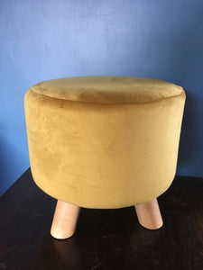 Small velvet footstool in mustard with three wooden legs