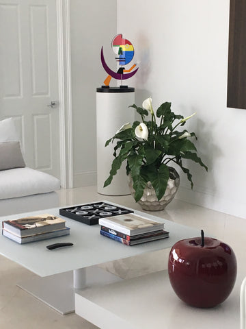 White laminate cylinder pedestal with whimsical sculpture to break up the otherwise hard edges of the room.