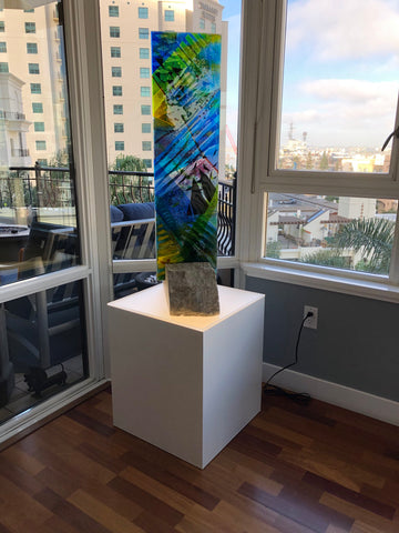White laminate cube table with ambient light surface displaying glass sculpture
