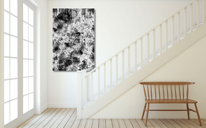 Large metal print hanging near stairs. Abstract is balck and white with a lot of dripping paint.