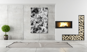 Large metal print of black & white abstract. Room is very modern with a fireplace, small plant, stacked logs and simple rug on marble floor.