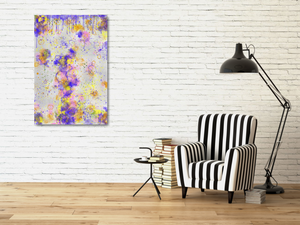 Metal print hanging on white brick near a black and white chair. Abstract tha tlooks like old layers of paint, with cracks. Green, silver, blue, yellow, orange, and pink.