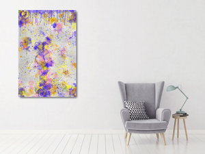 Metal print in a white room with a pale gray chair. Abstract tha tlooks like old layers of paint, with cracks. Green, silver, blue, yellow, orange, and pink.
