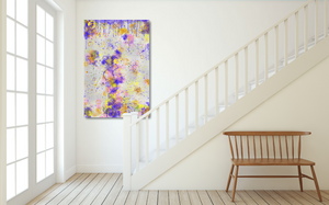 Metal print at the bottom of a white staircase. Abstract tha tlooks like old layers of paint, with cracks. Green, silver, blue, yellow, orange, and pink.
