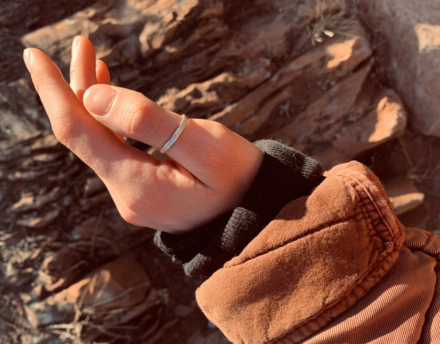 hand shown in front of red rocks in a silver thumb ring with an earthy red jacket sleeve