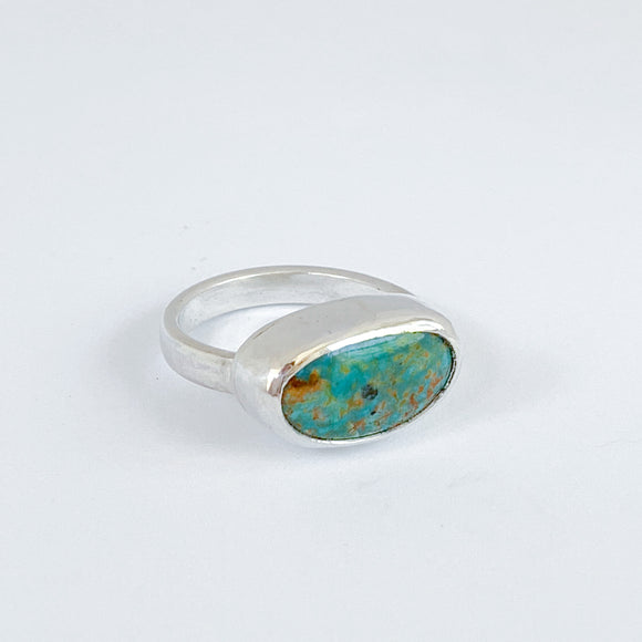 Handmade turquoise ring. Simple bezel set horizontal ring. Bean shaped turquoise cabochon with deep teal coloring.