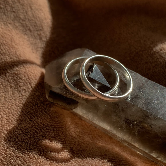 A pair of silver stacking rings sunbathing on a quartz crystal, with a brown background.