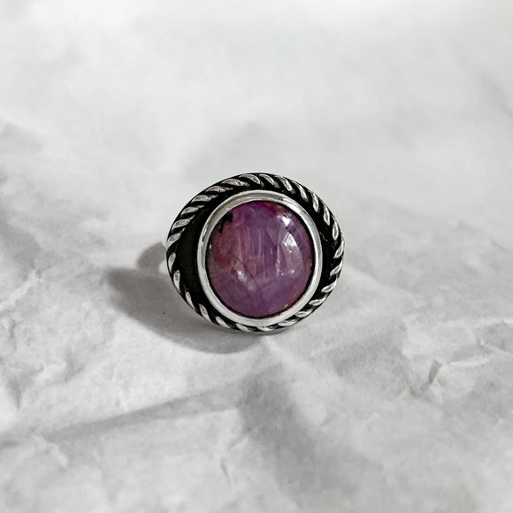 Maroon sapphire stone in a silver bezel set ring. Twisted wire border. Eye shaped stone ring with sapphire
