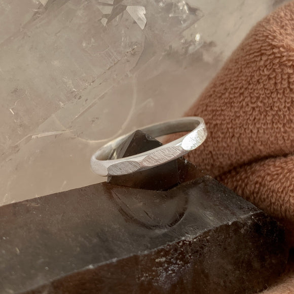 Geometric stacking ring with hand-filed facets. The traditional metalsmithing tools show in the file marks on the handmade silver band. The half-round ring band balances on a dark smoky quartz crystal. Brown terry cloth in the right of the image, and clear quartz towards the top left.