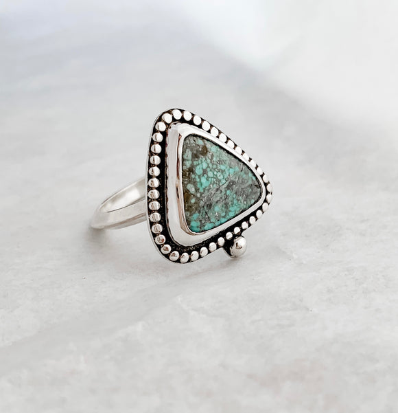 Handcrafted turquoise and silver ring with a triangular stone. The webbed blue turquoise is in a simple bezel setting, with a hammered dot border and thin triangular band. High-shine sterling silver on a white background.