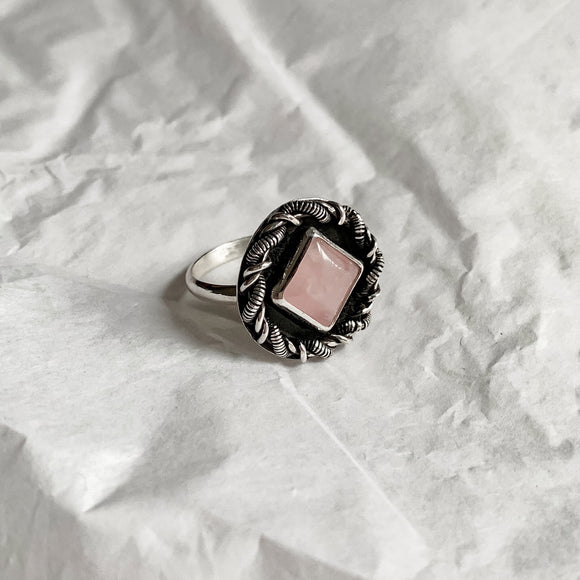 One of a kind silver and rose quartz ring. A square shaped rose quartz cabochon with unique wire wrapped border, and a dark patina to contrast the polished silver.
