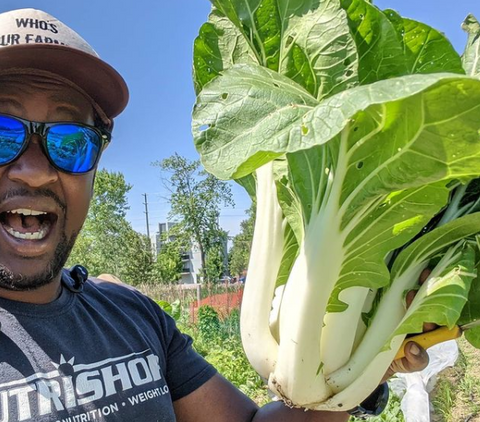 man with sunglasses holding large bok choy